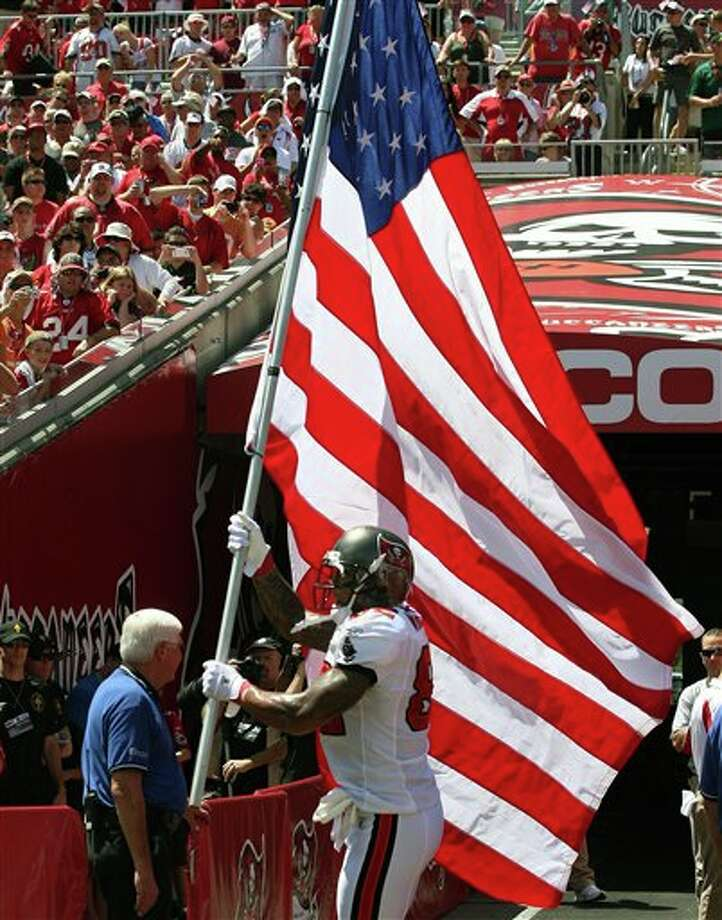 Tampa Bay Buccaneers tight end Kellen Winslow (82) carries a large American flag as he runs onto the field during player introcutions before an NFL football game against the Detroit Lions Sunday, Sept. 11, 2011, in Tampa, Fla. (AP Photo/Margaret Bowles) Photo: Associated Press