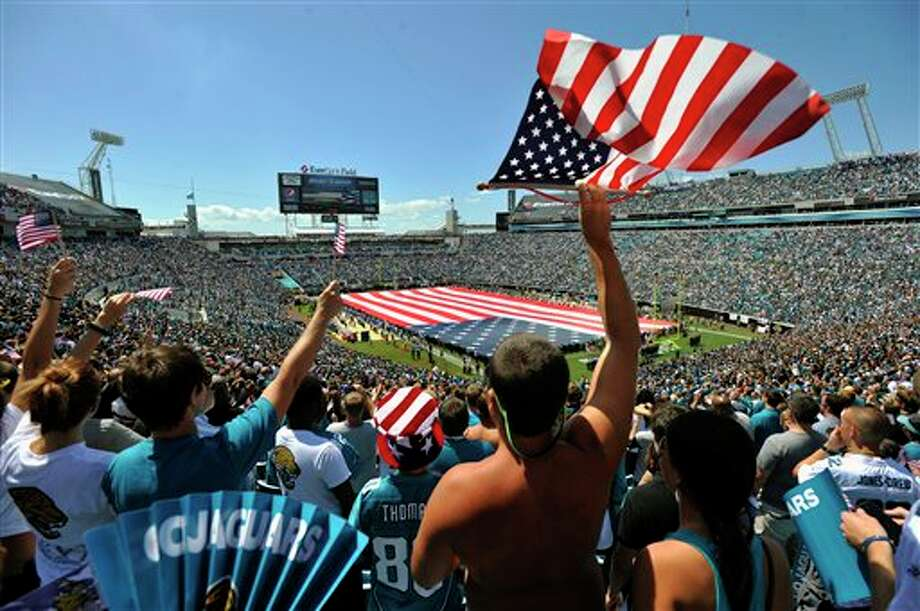 Fans cheer during a ceremony in commemoration of the 10th anniversary of the 9/11 terrorist attacks before an NFL football game between the Jacksonville Jaguars and the Tennessee Titans, Sunday, Sept. 11, 2011, in Jacksonville, Fla. (AP Photo/Stephen Morton) Photo: Associated Press