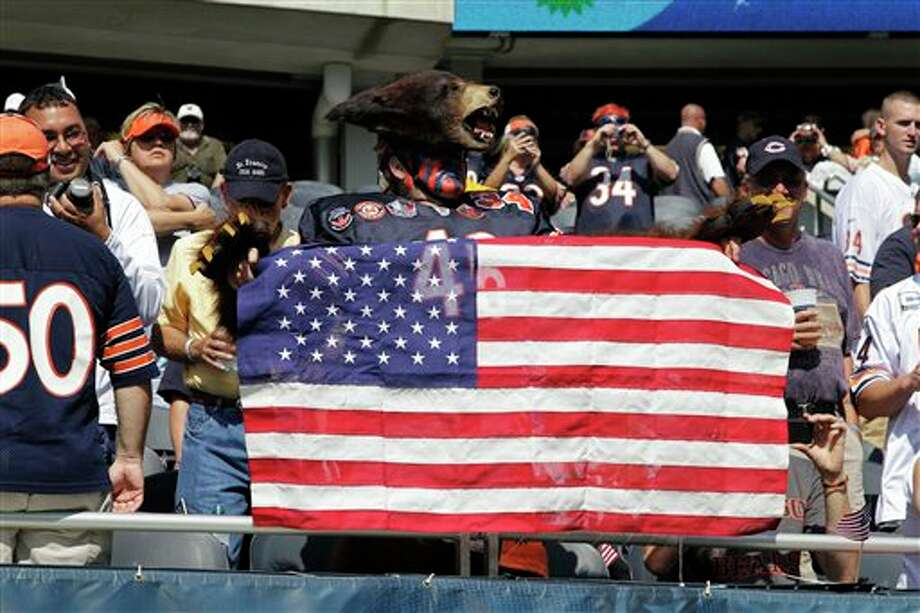 A Chicago Bears fan holds up an American flag during warm-ups before an NFL football game between the Bears and Atlanta Falcons in Chicago, Sunday, Sept. 11, 2011. The day marks the 10th anniversary of the Sept. 11 attacks. (AP Photo/Nam Y. Huh) Photo: Associated Press