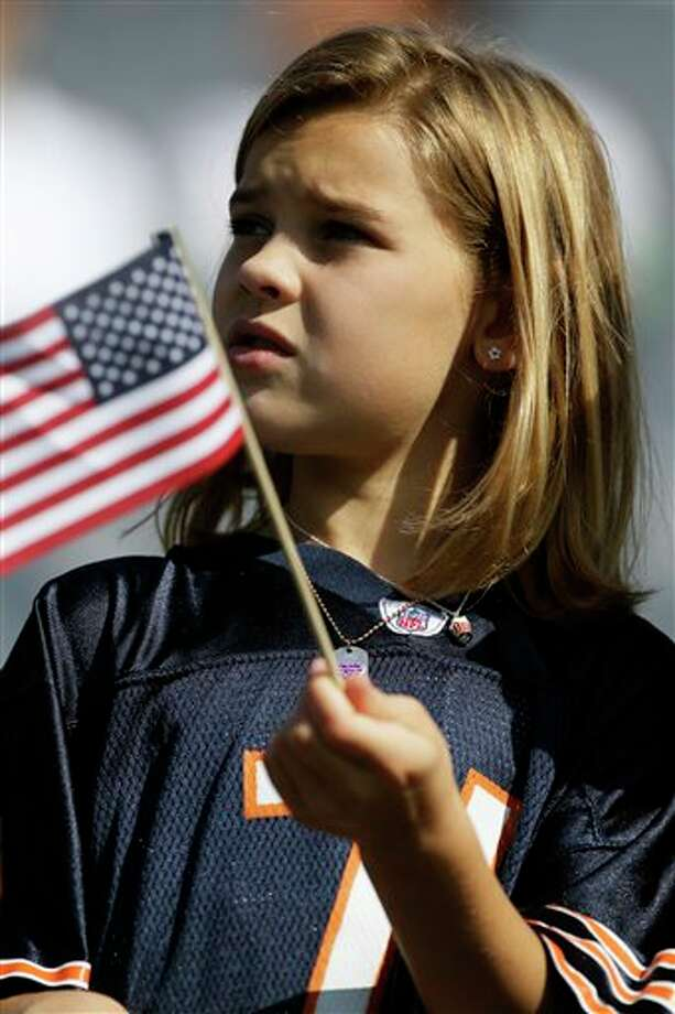 Kaitlyn Speck waves an American flag before an NFL football game between the Chicago Bears and Atlanta Falcons in Chicago, Sunday, Sept. 11, 2011. (AP Photo/Nam Y. Huh) Photo: Associated Press