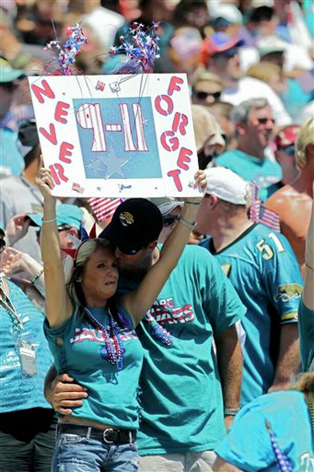 A Jacksonville Jaguars fan holds up a sign during a 9-11 ceremony before an NFL football game between the Jacksonville Jaguars and the Tennessee Titans, Sunday, Sept. 11, 2011, in Jacksonville, Fla. (AP Photo/John Raoux) Photo: Associated Press