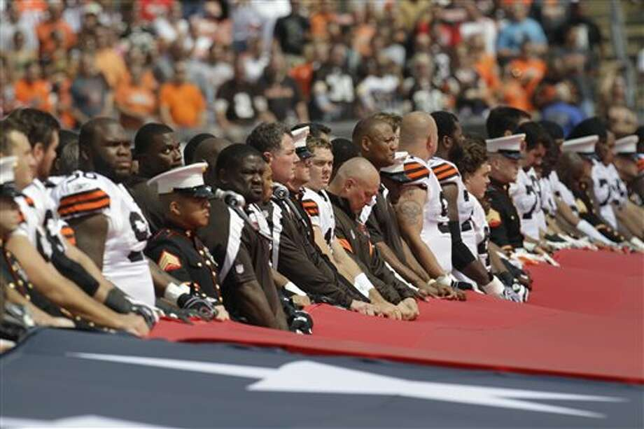 Cleveland Browns quarterback Colt McCoy, center, along with other members of the Browns, fire department and armed services hold a United States flag during the national anthem before an NFL football game against the Cincinnati Bengals, Sunday, Sept. 11, 2011, in Cleveland. (AP Photo/Tony Dejak) Photo: Associated Press
