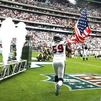 Houston Texans linebacker DeMeco Ryans (59) takes the field carrying the American flag before an NFL football game against the Indianapolis Colts at Reliant Stadium Sunday, Sept. 11, 2011, in Houston. Photo: Brett Coomer, Houston Chronicle / © 2011 Houston Chronicle