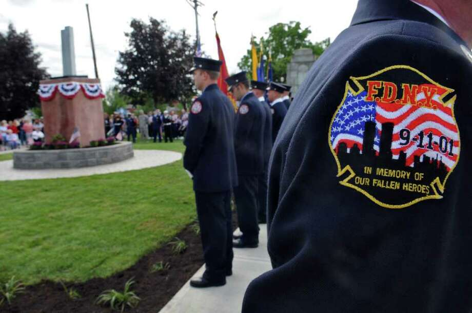 Retired Troy Fire Department Lt. Phil Quandt honors those lost by the Fire Department of New York during the World Trade Center attack of 2001,  during the Celebration of Freedom, the dedication and memorial service of the Troy September 11th Memorial at 112th Street and First Avenue on Sunday Sept. 11, 2011 in Troy, NY.  The patch was given to him by a friend who is a New York City firefighter. ( Philip Kamrass / Times Union) Photo: Philip Kamrass / 00014568A