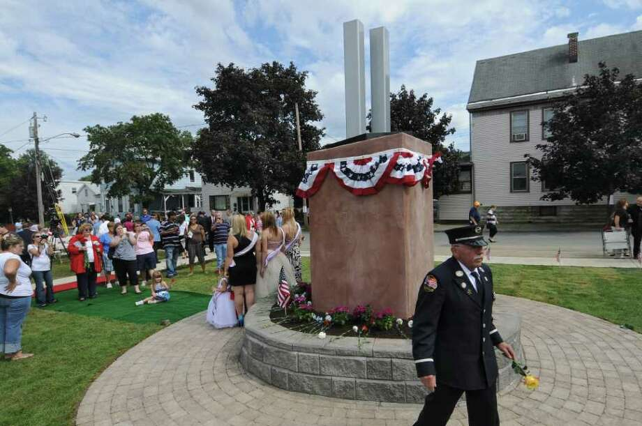 Retired Troy Fire Department Lt. Phil Quandt carries a flower during the  Celebration of Freedom, the dedication and memorial service of the Troy Sept. 11 Memorial at 112th Street and First Avenue on Sunday Sept. 11, 2011, in Troy, NY.  ( Philip Kamrass / Times Union) Photo: Philip Kamrass / 00014568A