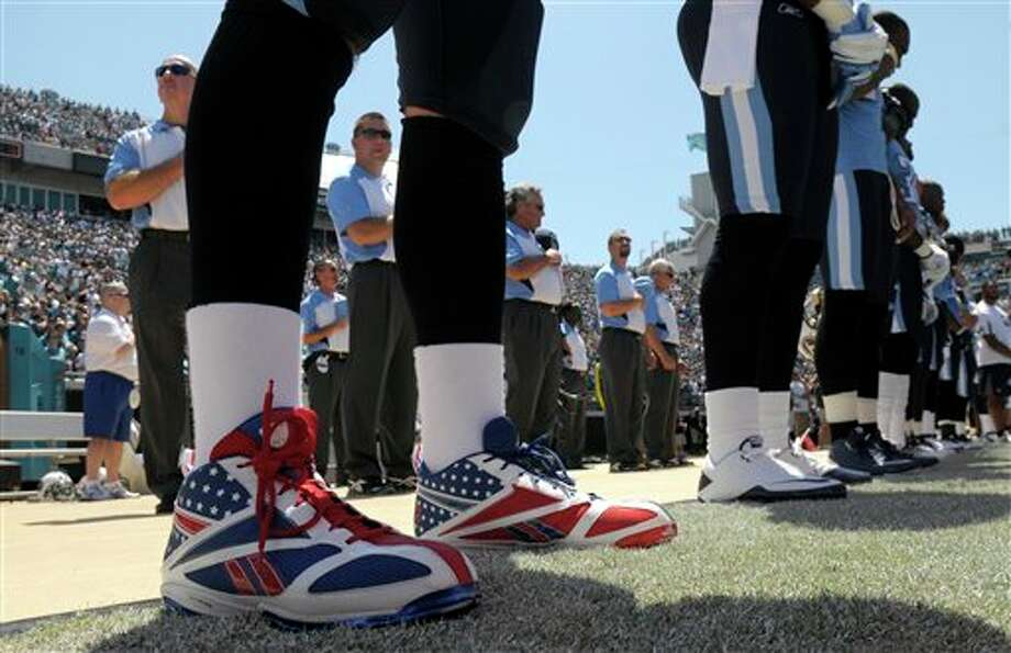 Tennessee Titans quarterback Matt Hasselbeck, left, wears shoes made to look like the American flag prior to an NFL football game against the Jacksonville Jaguars in Jacksonville, Fla., Sunday, Sept. 11, 2011.(AP Photo/PHELAN EBENHACK) Photo: Associated Press