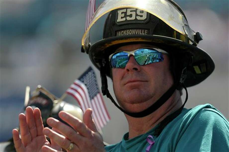 A firefighter cheers for the Jacksonville Jaguars while wearing his helmet during the second half of an NFL football game against the Tennessee Titans in Jacksonville, Fla., Sunday, Sept. 11, 2011.(AP Photo/Phelan M. Ebenhack) Photo: Associated Press