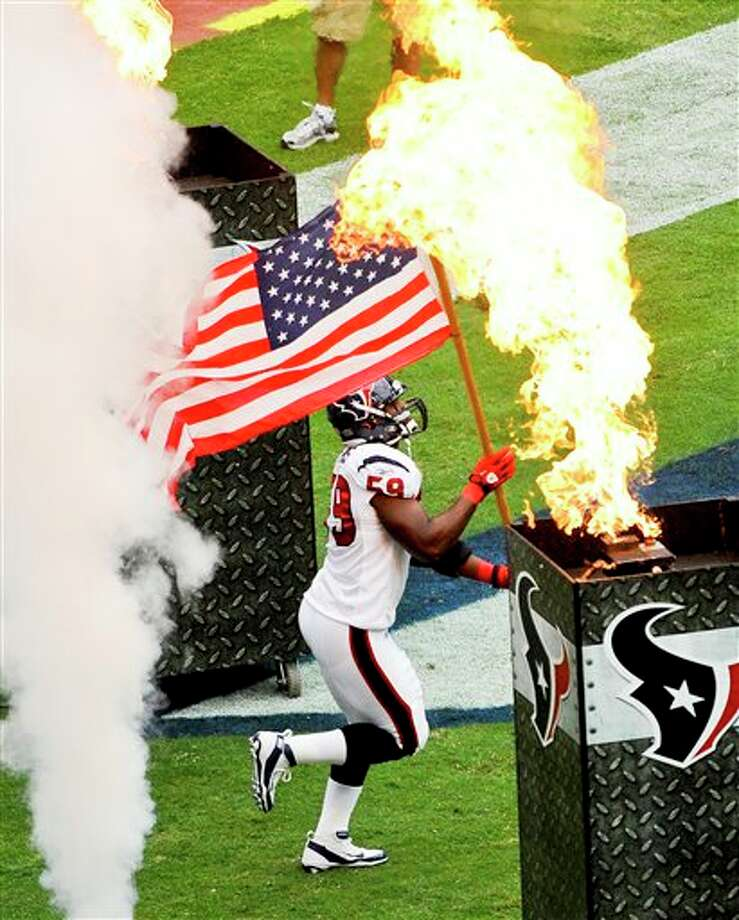 Houston Texans' DeMeco Ryans carries a flag onto the field before an NFL football game against the Indianapolis Colks Sunday, Sept. 11, 2011, in Houston. (AP Photo/Dave Einsel) Photo: Associated Press