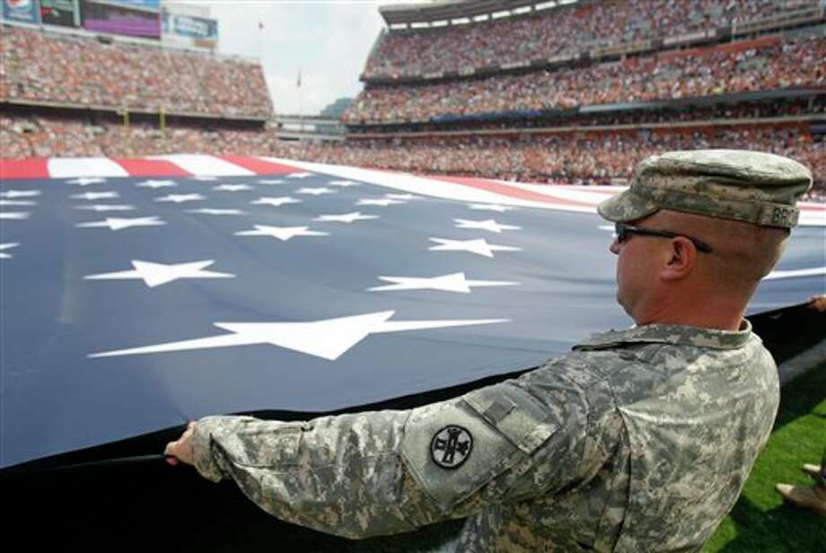US Army staff Sgt. Erick Browning holds a flag during the opening ceremonies before an NFL football game between the Cleveland Browns and the Cincinnati Bengals Sunday, Sept. 11, 2011, in Cleveland. (AP Photo/Tony Dejak) Photo: Associated Press