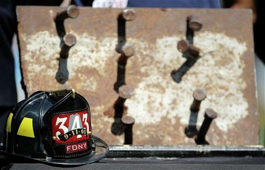 A piece of steel from the World Trade Center and a NY Fire Department hat are displayed in a tribute for the tenth anniversary of Sept. 11 before the San Diego Chargers play the Minnesota Vikings in an NFL football game Sunday, Sept. 11, 2011, in San Diego.  (AP Photo/Gregory Bull) Photo: Associated Press