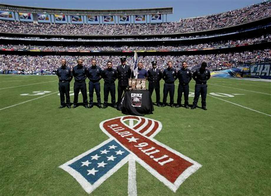 Members of the New York Fire Department pause during a moment of silence for the tenth anniversary of Sept. 11 before the NFL football game between the San Diego Chargers and Minnesota Vikings Sunday, Sept. 11, 2011, in San Diego.  (AP Photo/Gregory Bull) Photo: Associated Press