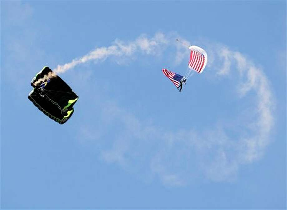 A parachuter with an American flag emerges lands at Qualcomm Stadium  during a tribute for the tenth anniversary of Sept. 11 before the San Diego Chargers face the Minnesota Vikings in an NFL football game Sunday, Sept. 11, 2011, in San Diego.  (AP Photo/Gregory Bull) Photo: Associated Press