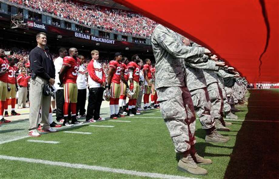 San Francisco 49ers head coach Jim Harbaugh, left, listens during pregame 9/11 ceremonies before an NFL football game against the Seattle Seahawks in San Francisco, Sunday, Sept. 11, 2011. (AP Photo/Paul Sakuma) Photo: Associated Press