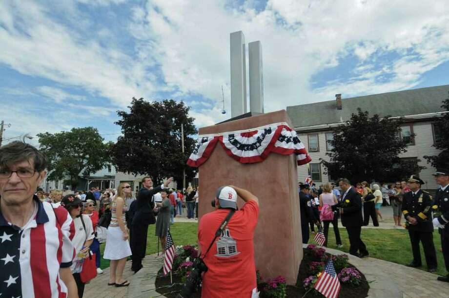 James R. Gordon, to left of the memorial, tosses a flower during the  Celebration of Freedom, the dedication and memorial service of the Troy Sept. 11 Memorial at 112th Street and First Avenue on Sunday Sept. 11, 2011, in Troy, NY.   Gordon is Chairman of the memorial's coordinating committee. ( Philip Kamrass / Times Union) Photo: Philip Kamrass / 00014568A
