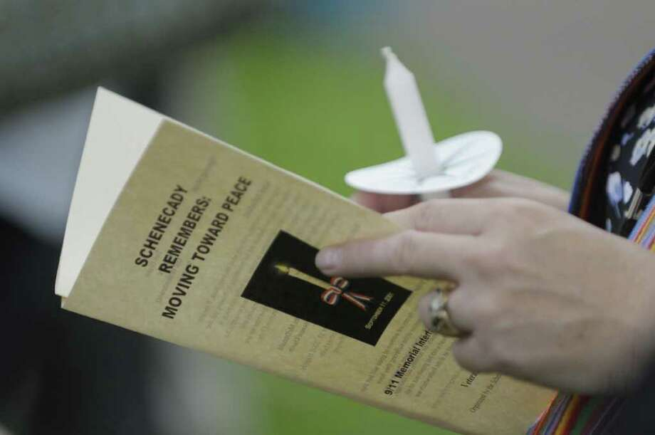 "A woman looks through a program during a 9/11 Interfaith Service called ""Schenectady Remembers: Moving Toward Peace"" held at Veterans Park on Sunday, Sept. 11, 2011, in Schenectady.   (Paul Buckowski / Times Union) Photo: Paul Buckowski / 00014576A"