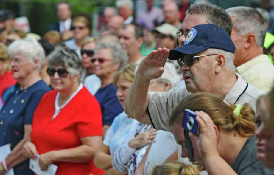 Those in attendance honor the flag during the Celebration of Freedom, the dedication and memorial service of the Troy September 11th Memorial at 112th Street and First Avenue on Sunday Sept. 11, 2011 in Troy, NY.   ( Philip Kamrass / Times Union) Photo: Philip Kamrass / 00014568A