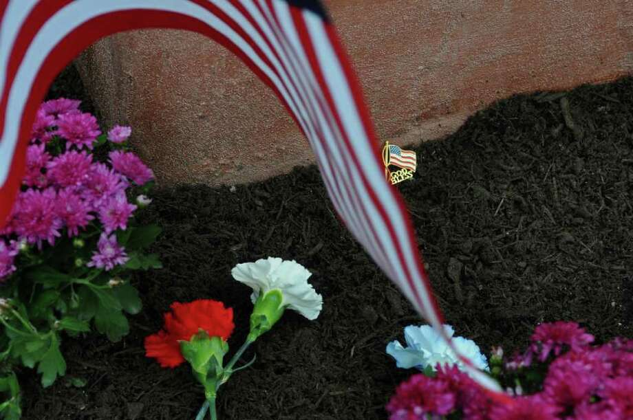 A pin among the flowers placed during the Celebration of Freedom, the dedication and memorial service of the Troy September 11th Memorial at 112th Street and First Avenue on Sunday Sept. 11, 2011 in Troy, NY.   ( Philip Kamrass / Times Union) Photo: Philip Kamrass / 00014568A