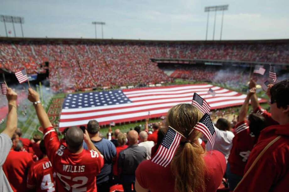 A giant American flag is spread across the field during the singing of the national anthem before the San Francisco 49ers' season opener against the Seattle Seahawks at Candlestick Park in San Francisco on Sunday, Sept. 11, 2011. Photo: Ezra Shaw, Getty Images / 2011 Getty Images