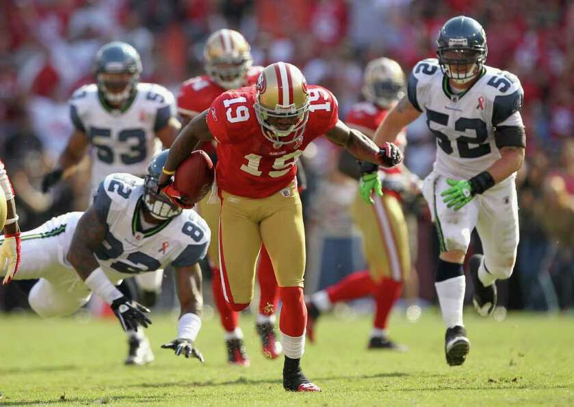 Ted Ginn #19 of the San Francisco 49ers breaks a tackle on his way to returning a punt for a touchdo