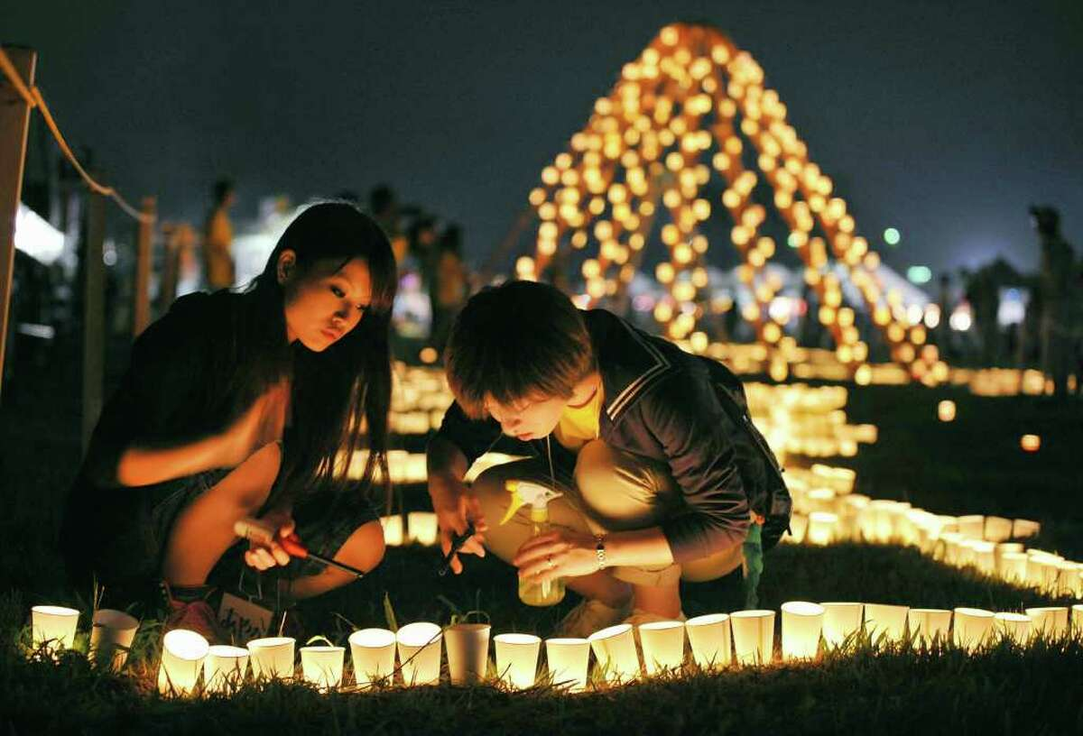 Local residents light a candle at a park during a memorial event marking six months after the March 11 earthquake and tsunami in Iwanuma city, Miyagi prefecture, Sunday, Sept. 11, 2011. As the world commemorates the 10th anniversary of the World Trade Center attacks, Sunday is doubly significant for Japan. It marks exactly six months since the disasters. (AP Photo/Kyodo News) JAPAN OUT, MANDATORY CREDIT, NO LICENSING IN CHINA, FRANCE, HONG KONG, JAPAN AND SOUTH KOREA