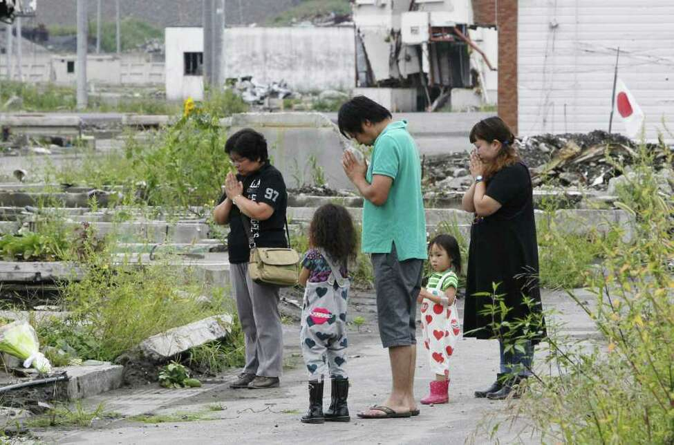 Standing in the rubble of a residential area a family pray for their loved ones who died in the March 11 earthquake and tsunami as a siren informs townspeople the exact time of the massive quake in Otsuchi, Iwate Prefecture, northeastern Japan, Sunday, Sept. 11, 2011. As the world commemorates the 10th anniversary of the World Trade Center attacks, Sunday is doubly significant for Japan. It marks exactly six months since the disasters. (AP Photo/Kyodo News) JAPAN OUT, MANDATORY CREDIT, NO LICENSING IN CHINA, FRANCE, HONG KONG, JAPAN AND SOUTH KOREA