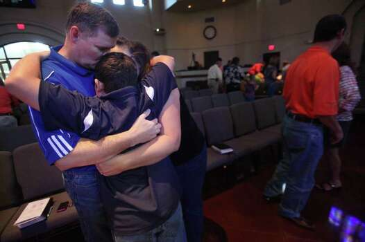Jeff Collins, 50, embraces wife Elena, 41, and son Cody, 11, after services at Wildwood United Methodist Church on Sunday, Sept. 11, 2011, in Magnolia.  The church observed the Sept. 11th attacks anniversary and prayed for fire victims in the tri-county wildfires. Photo: Mayra Beltran, Houston Chronicle / © 2011 Houston Chronicle