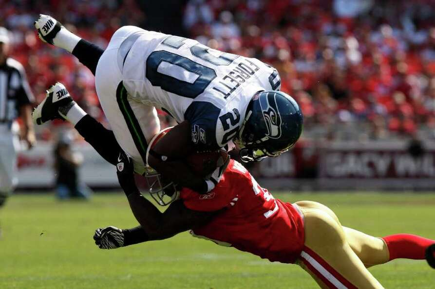 Seattle Seahawks running back Justin Forsett gets tackled by a San Francisco 49ers defender during t