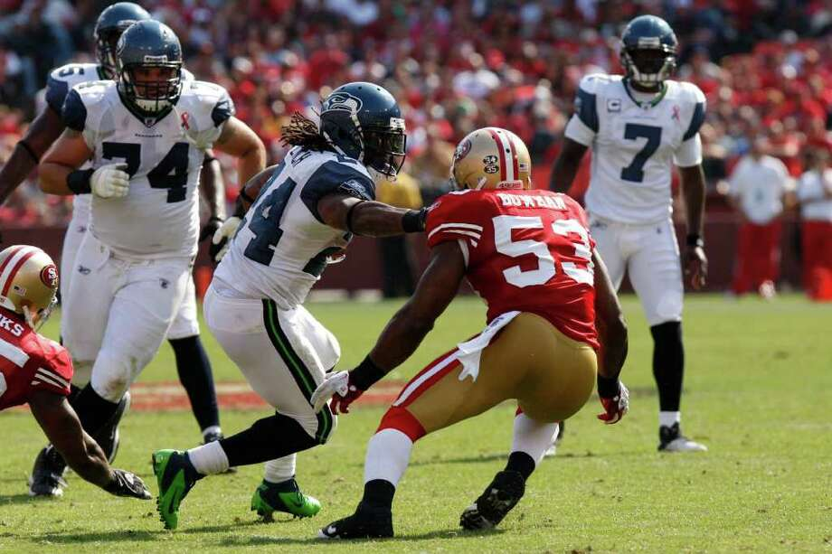 Seattle Seahawks running back Marshawn Lynch tries to escape San Francisco 49ers NaVorro Bowman during the fourth quarter of the San Francisco 49ers vs. Seattle Seahawks game at Candlestick Park in San Francisco, Calif. on Saturday, Sept. 10, 2011. Photo: Dylan Entelis, The Chronicle / ONLINE_YES