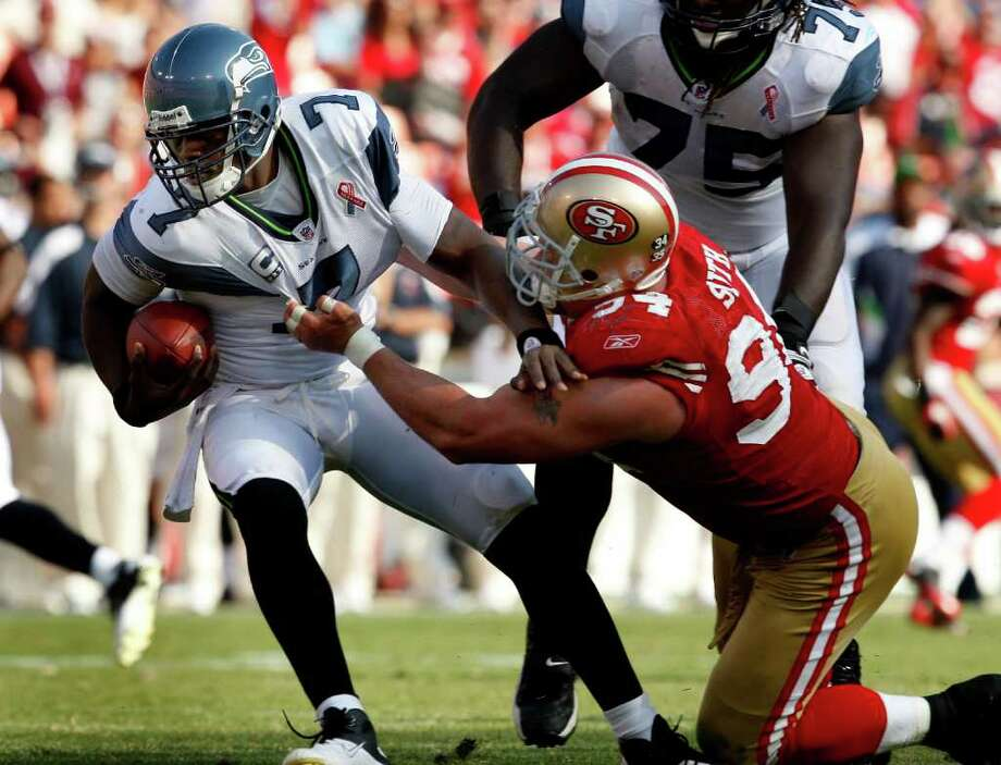 Justin Smith takes down Seahawk quarterback Tarvaris Jackson in the first half. The San Francisco 49ers defeat the Seattle Seahawks 33-17 at Candlestick Park Sunday September 11, 2011. Photo: Brant Ward, The Chronicle / ONLINE_YES
