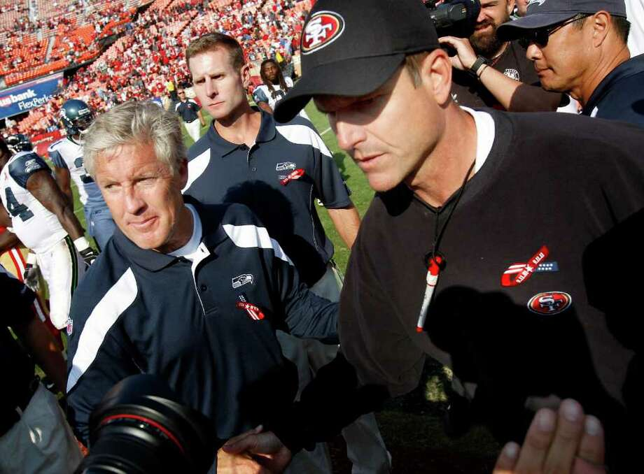 Seahawks coach Pete Carroll (left) and 49ers coach Jim Harbaugh meet at midfield after the game. The San Francisco 49ers defeat the Seattle Seahawks 33-17 at Candlestick Park Sunday September 11, 2011. Photo: Brant Ward, The Chronicle / ONLINE_YES