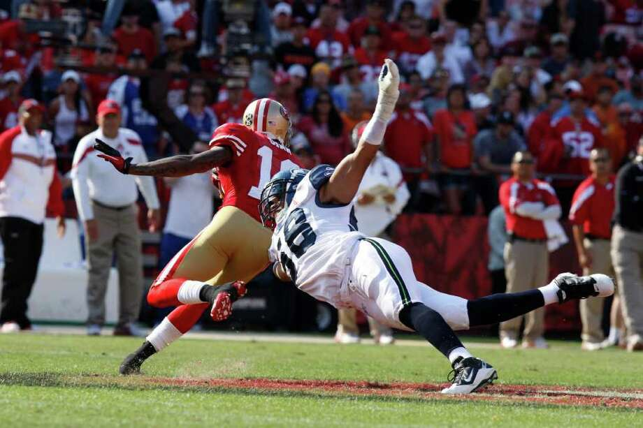 San Francisco 49ers wide receiver Ted Ginn avoids Seattle Seahawks linebacker Leroy Hill during the San Francisco 49ers vs. Seattle Seahawks game at Candlestick Park in San Francisco, Calif. on Saturday, Sept. 10, 2011.  Ginn returned a kickoff and a punt for a touchdown in the fourth quarter. Photo: Dylan Entelis, The Chronicle / ONLINE_YES
