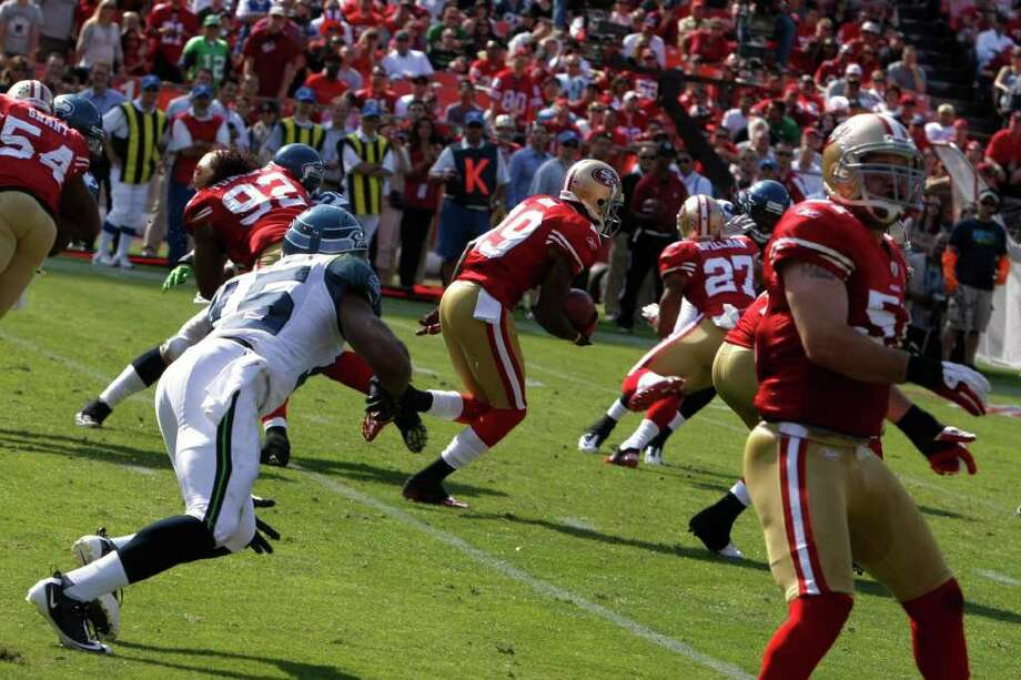 San Francisco 49ers wide receiver Ted Ginn avoids tacklers during the fourth quarter of the San Francisco 49ers vs. Seattle Seahawks game at Candlestick Park in San Francisco, Calif. on Saturday, Sept. 10, 2011.  Ginn returned both a kickoff and a punt for touchdowns in the fourth quarter. Photo: Dylan Entelis, The Chronicle / ONLINE_YES