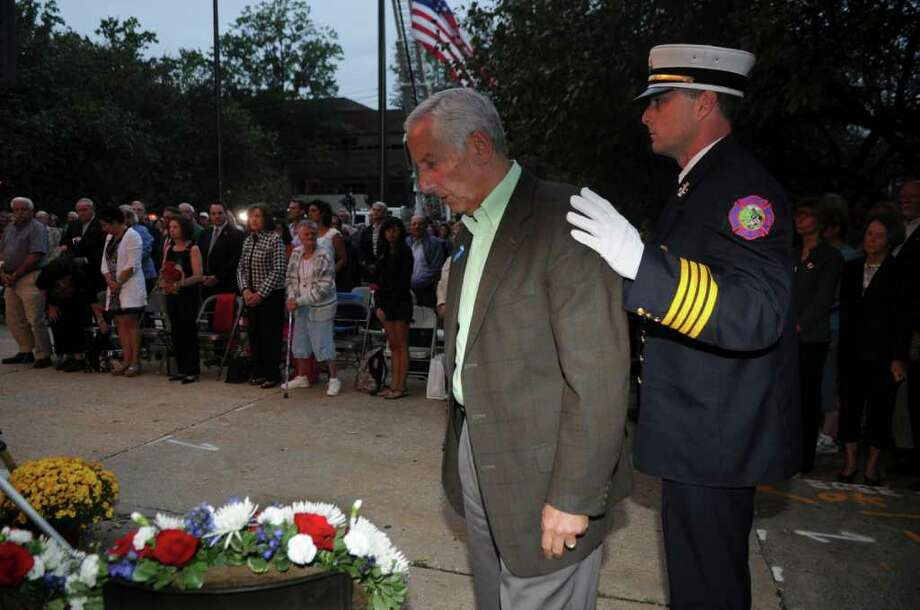 Ralph Sabbag, left, whose son Jason was killed in the twin towers in 9/11, prepares to place a wreath with help Fire Chief Robert Kick at Greenwich's September 11th to honor the memory of those lost on 9/11, especially the 23 residents who died, in a ceremony in front of the Greenwich Town Hall on Sept. 11, 2011. Photo: Helen Neafsey / Greenwich Time