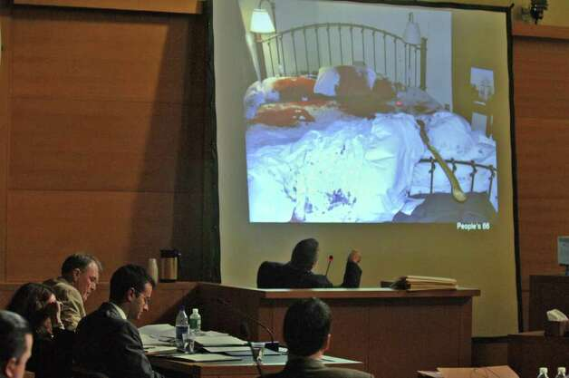 Christopher Porco, lower left, with glasses, avoids looking on as New York State Police Investigator Drew McDonald describes the scene of the master bedroom of the Porco home in Delmar, N.Y., from the witness stand in the Orange County Courthouse in Goshen, N.Y., during Porco's trial Wednesday, July 5, 2006. The murder weapon, an ax, can be seen on the bed. (AP Photo/Philip Kamrass) Photo: PHILIP KAMRASS / POOL ALBANY TIMES UNION
