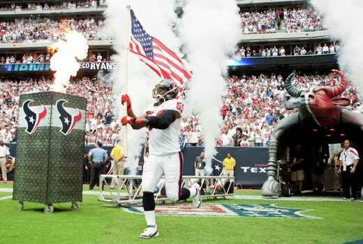 Houston Texans linebacker DeMeco Ryans waves an American flag when he's introduced before the Texan's game against the Indianapolis Colts. Photo: Nick De La Torre, Houston Chronicle / © 2011 Houston Chronicle
