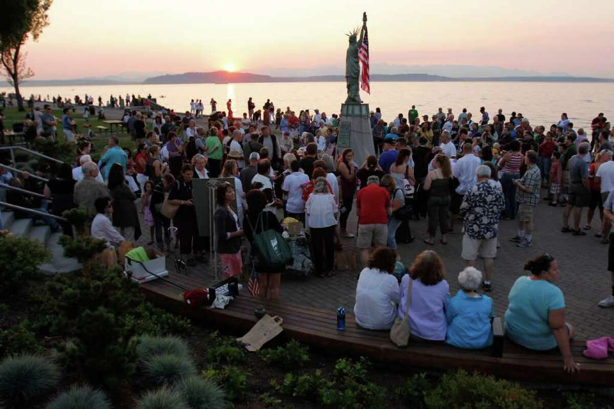 People gather around the Alki Statue of Liberty Plaza in Seattle on Sunday, Sept. 11, 2011 in remembrance of the victims of the 9/11 terrorist attacks.
