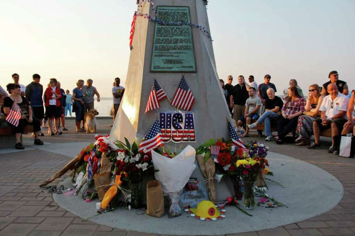People pay their respects at the Alki Statue of Liberty.