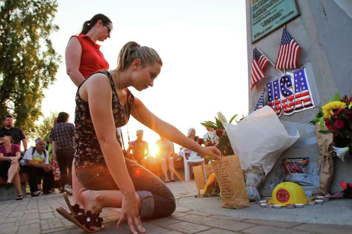 Shantel Gunter examines one person's contribution to the vigil at the Alki Statue of Liberty Plaza.