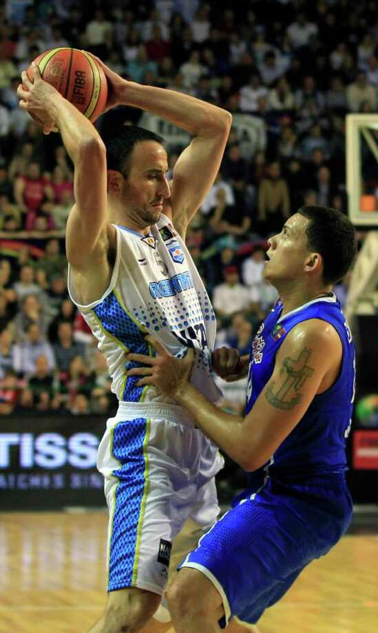 Argentina's Manu' Ginobili, left, looks to pass the ball as he is ball defended by Puerto Rico's Manuel Narvaez in their FIBA Americas Championship semi-final basketball game in Mar del Plata, Argentina, Saturday Sept. 10, 2011. Photo: Martin Mejia/Associated Press