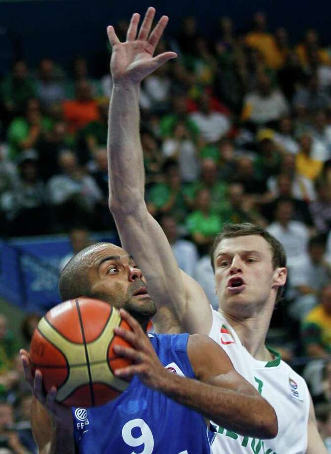 France's Tony Parker, left, challenges for the ball with Lithuania's Martynas Pocius, during their EuroBasket European Basketball Championship Group E match in Vilnius, Lithuania, Friday Sept. 9, 2011. Photo: Darko Vojinovic/Associated Press / AP