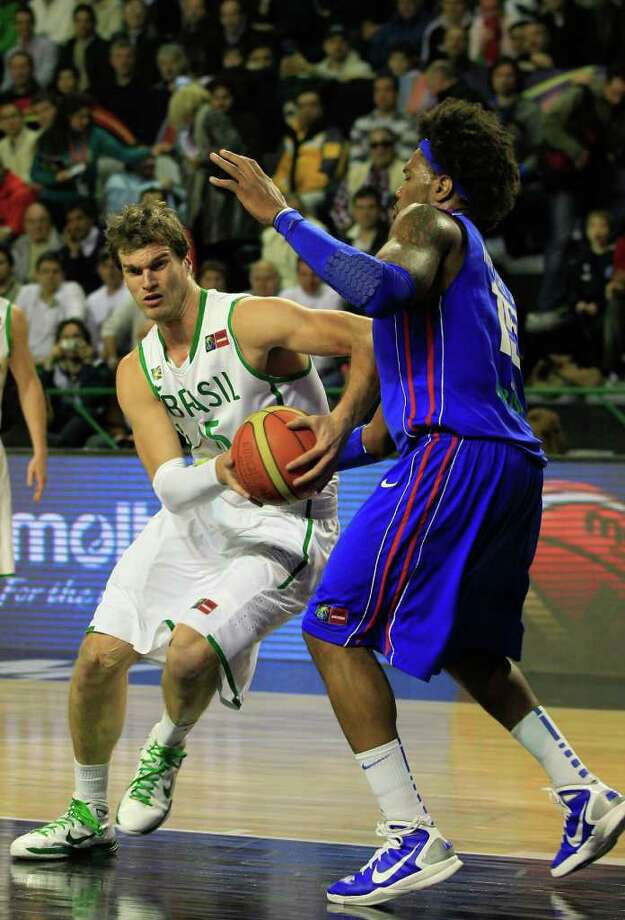 Brazil's Tiago Splitter, left, attempts to dribble past Dominican Republic's Jack Martinez during a FIBA Americas Championship semi-final basketball game in Mar del Plata, Argentina, Saturday Sept. 10, 2011. Photo: Martin Mejia/Associated Press