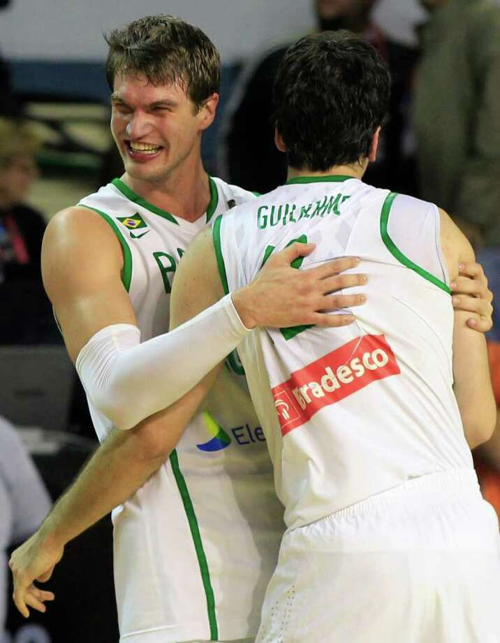 Brazil's Tiago Splitter, left, celebrates with teammate Guilherme Giovannoni after defeating the Dominican Republic 83-76 during their FIBA Americas Championship semi-final basketball game in Mar del Plata, Argentina, Saturday Sept. 10, 2011. Photo: Martin Mejia/Associated Press