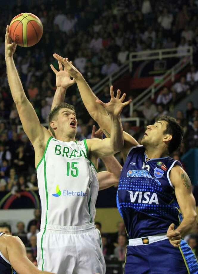 Brazil's' Tiago Splitter, left, shoots against Argentina's Carlos Delfino in their FIBA Americas Championship first place basketball game in Mar del Plata, Argentina, Sunday Sept. 11, 2011. Argentina went on to defeat Brazil 80-75. Photo: Martin Mejia/Associated Press
