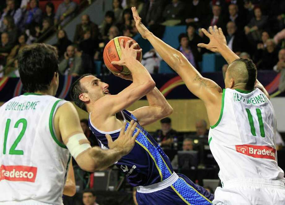 Argentina's Manu Ginobili, center, shoots against Brazil's Rafael Hettsheimer, right, and Guilherme Giovannoni, left, in their FIBA Americas Championship final basketball game in Mar del Plata, Argentina, Sunday Sept. 11, 2011. Photo: Martin Mejia/Associated Press