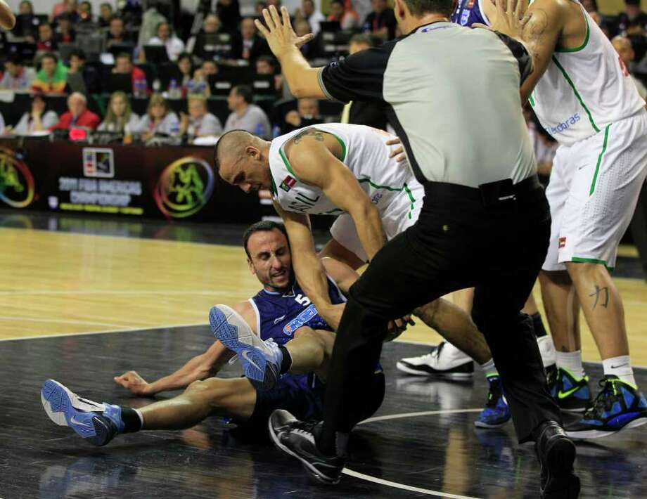 Argentina's Manu Ginobili, left center, on floor, fights for possession of the ball with Brazil's Alex Garcia during their FIBA Americas Championship first place basketball game in Mar del Plata, Argentina, Sunday Sept. 11, 2011. Argentina went on to defeat Brazil 80-75. Photo: Martin Mejia/Associated Press