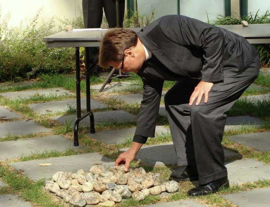 The Rev. Matthew Calkins, rector of St. Timothyís Episcopal Church, places a memorial stone in a pile on the ground at Fairfield's historic Town Hall Green on Sunday during a memorial service for victims of the Sept. 11, 2001, terrorist attacks. Photo: Meg Barone / Fairfield Citizen freelance