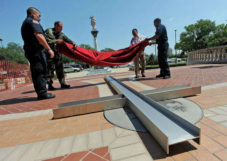 From left, Danny Valdez with the Beaumont Polic Department, Lee Williams with the U.S. Army, Max Nguyen with Beaumont EMS and Reginald Phillips with the Beaumont Fire Department uncover an i-beam cross during a 9/11 ceremony at St. Anthony Cathedral Basilica on Sunday. Photo: Guiseppe Barranco
