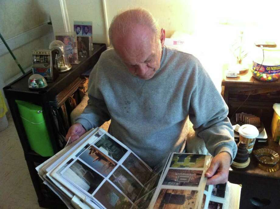 Tom Kessel shows off one of his binders of photos that he has taken over the past 40 years. Photo: Ben Holbrook