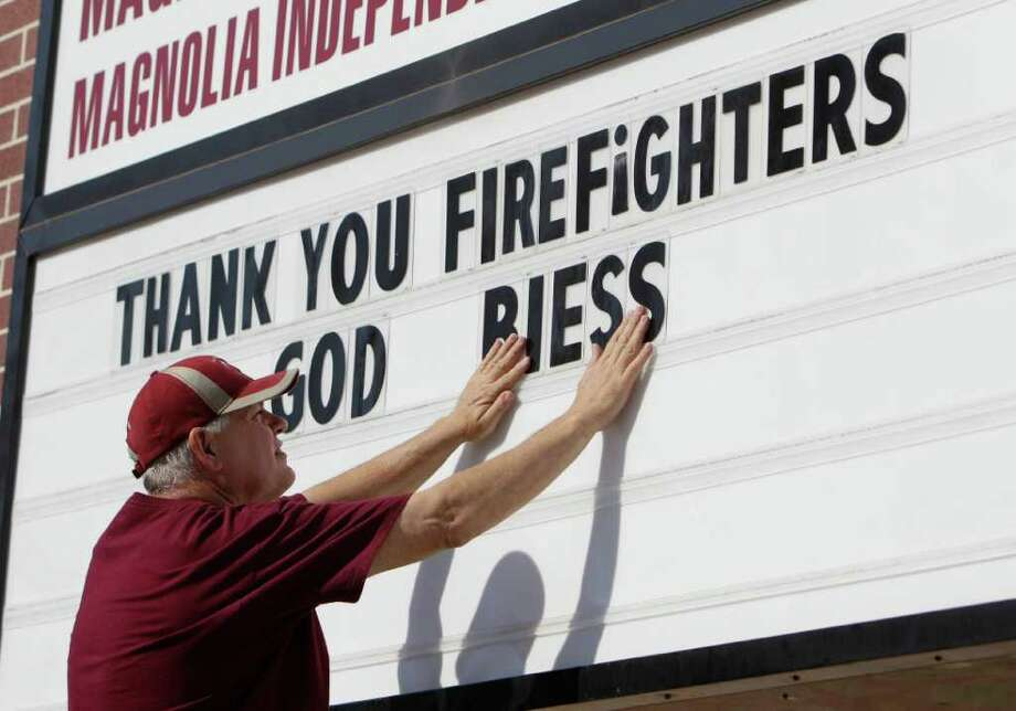 Magnolia Parkway Elementary employee John Tramutolo posts his sentiments toward tireless firefighters. The school on FM 1488 had been closed because of the wildfires. Photo: Melissa Phillip / © 2011 Houston Chronicle