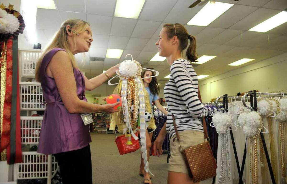 JERRY BAKER: FOR THE CHRONICLE BUILDING TRADITION: Lauren DeLorimier, left, owner of the Homecoming Super Store in The Woodlands, admires the decorations of Cailey Chenault, 16, a junior at The Woodlands High School, on the mum that Cailey made for classmate Taylor Larza, a TWHS senior.